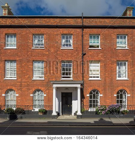 facade of the three-storey red brick building. White porch. Devon. UK