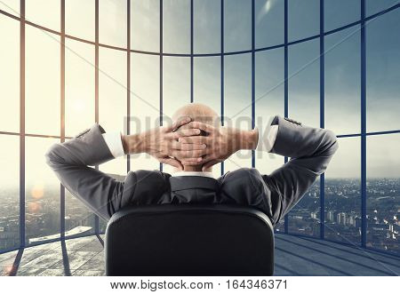 Businessman enjoys his professional success and watches the view over the city. Mixed media