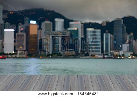 Opening wooden floor Hong Kong city blurred bokeh lights over Victoria Bay abstract background