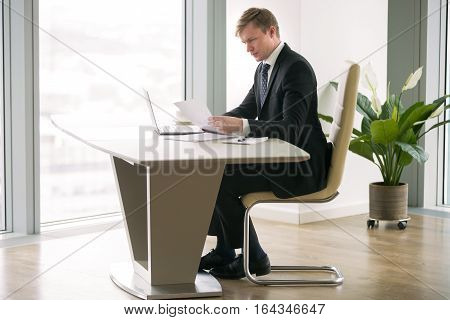 Young handsome businessman working with laptop at the desk in modern office, preparing business presentation, got new working place after climb the corporate ladder, paper work. Full length portrait