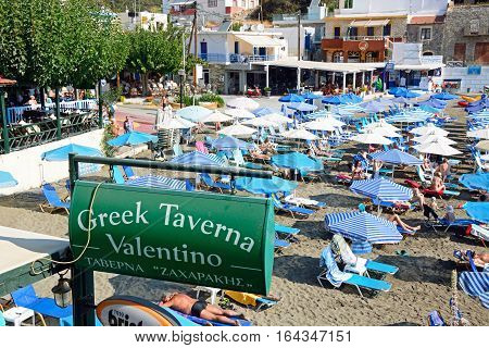 BALI, CRETE - SEPTEMBER 16, 2016 - Greek Taverna Valentino sign on the edge of the beach with tourists relaxing to the rear Bali Crete Greece Europe, September 16, 2016.