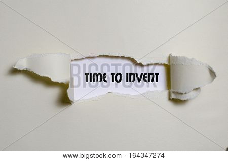The word time to invent appearing behind torn paper