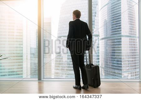 Young businessman with suitcase standing looking at full length window, dreaming to move only forward, high rental price, tenant looking for luxury home. Rear view. Business trip concept