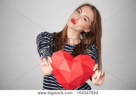 Beautiful smiling woman with red lips holding red polygonal paper heart shape sending a kiss
