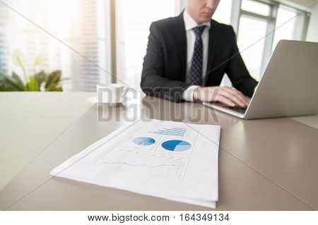 Close up of paper financial document with statistics, man dealing with business problems and the technology solutions, operations scaling, sales planning, strategy devising, developmental process