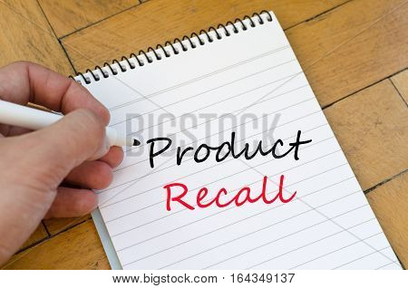 Human hand over wooden background and product recall text concept