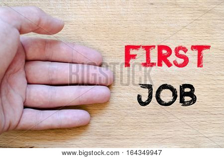 Human hand over wooden background and first job text concept