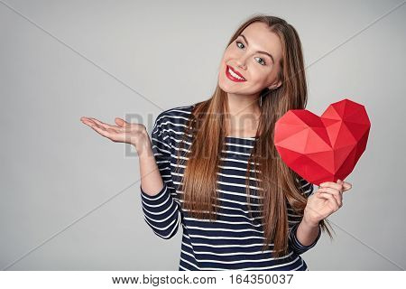 Smiling woman with red lips holding red polygonal paper heart shape showing open hand palm with copy space for product or text