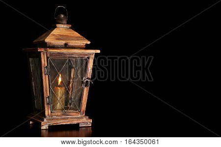 Old wooden lantern with burning candle isolated on black background.