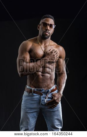 African American bodybuilder man, naked muscular torso, wearing jeans, isolated on black background