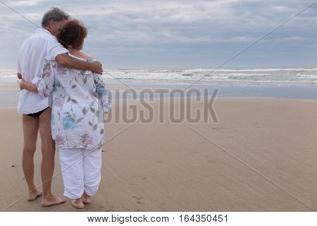 A Senior Couple Embracing On The Beach Vacation By The Sea