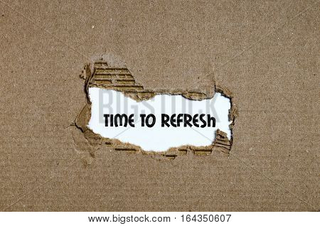 The word time to refresh appearing behind torn brown cardboard