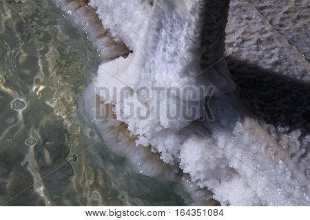 Salt formation on stilts wooden bridge in water Dead Sea.