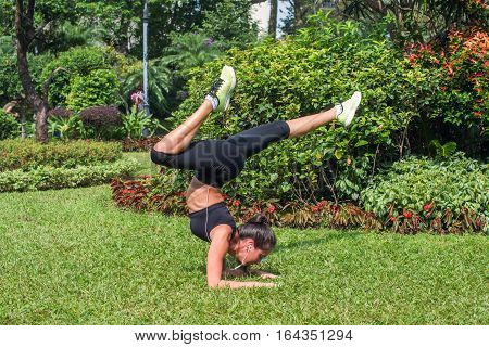 Sporty young woman doing handstand exercise with bending legs on grass in park. Fit girl practicing yoga outdoors