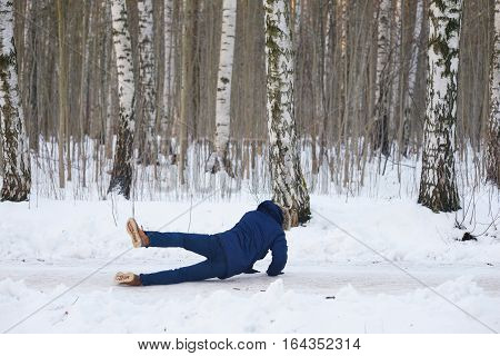 Young people in stylish clothes slipped on a slippery road during a walk on a birch grove. The guy fell and trying to stand up.