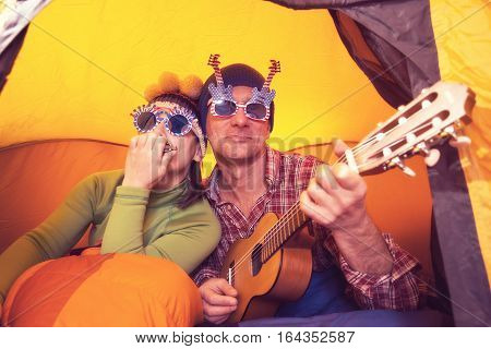 Joyful couple of hipsters in travel man with woman in the funny glasses playing ukulele and harmonica singing and having fun while they rest in camping.