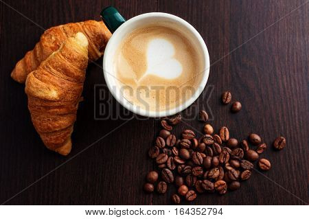 cup coffee and croissant on wooden background