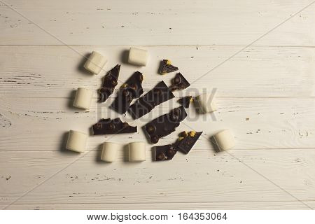 Peices of chocolate with nuts and white marshmallow on wooden background