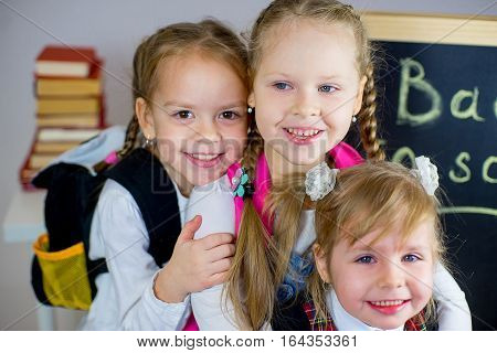Three Young Schoolgirls Near The Blackboard