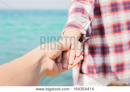 Couple summer vacation travel. Woman walking on romantic honeymoon promenade holidays holding hand of husband following her view from behind. (focus on hand)