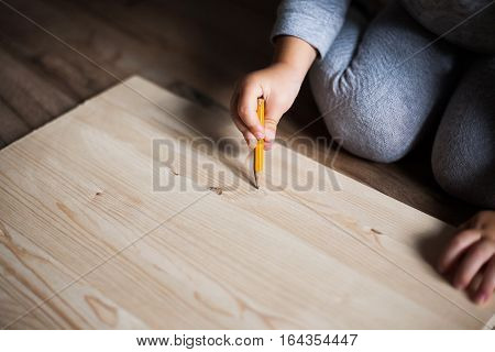 Little girl drawing on wooden panel with pencil