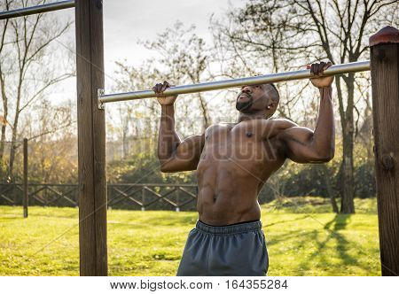Muscular Shirtless Hunky Black Man Outdoor in City Park. Showing Healthy Muscle Body While Looking away, Exercising and Working Out