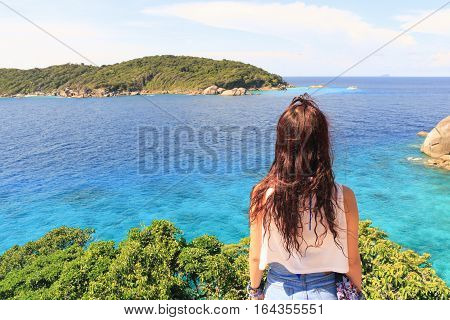 A young traveler girl sit on the top of mountain in Halong bay and enjoy the beauty of seascape. Young girl love wild life travel freedom.