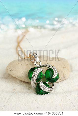 Jewellery pendant with emeralds on sand beach soft focus