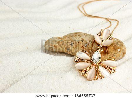 Golden jewellery pendant on sand beach soft focus