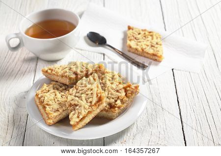 Cup of tea and shortbread cookies with jam for breakfast on white wooden table