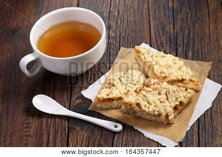 Cup of tea and homemade shortbread cookies with jam for breakfast on dark wooden table