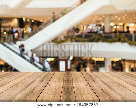 Wooden board empty table blurred background. Perspective brown wood table over blur in department store background - can be used for display or montage your products. Mock up for display of product.