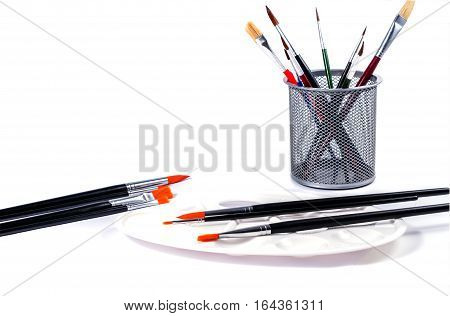 Colorful pencils in a glass and art palette with brushes . Isolated on white background.