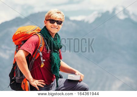 Smiling man tourist portrait with guide book on the mountain background