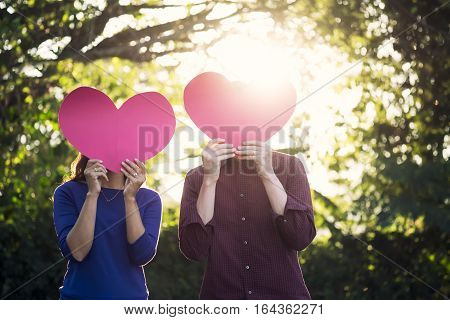 Young happy couple in love holding red paper heart in the garden. Love Romance and Valentine Concept idea.
