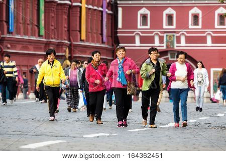 MOSCOW - SEPTEMBER 22 2015: Group of chinese tourists walking on the Red Square. This place is considered as the most popular sightseeng in Russia.