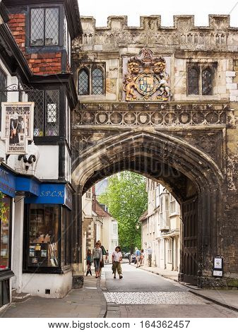 Salisbury Wilshire United Kingdom - June 18 2006: The famous medieval city North Gate known as the High Street Gate to the Cathedral Close. Tourists walk along High Street leading to Salisbury Cathedral.