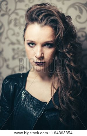 Punk rock style or halloween make-up. Fashion woman model face with bright glamour makeup. Perfect skin, black gloss eyeshadows on eyes and dark brown glossy lips visage. Vintage colours.