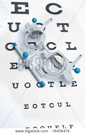 optometry concept - sight measuring spectacles & eye chart