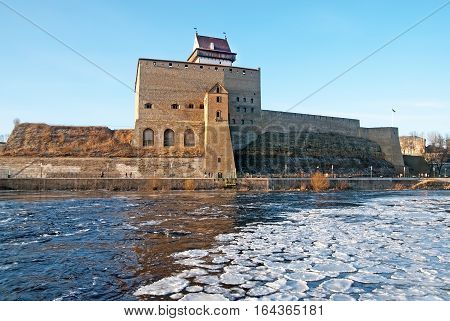 NARVA, ESTONIA - JANUARY 3, 2017: Hermann Castle Museum on the bank of The Narva (Narova) River. The River is a border between Estonia and Russia. View from Russian territory