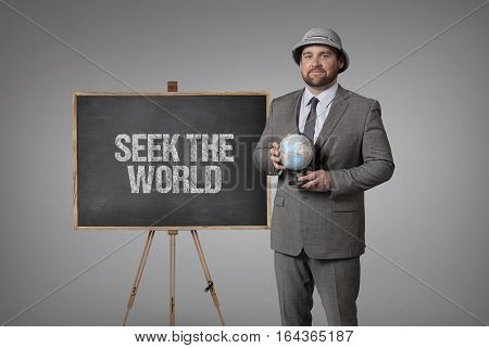 Seek the world text on blackboard with businessman holding globe in hands