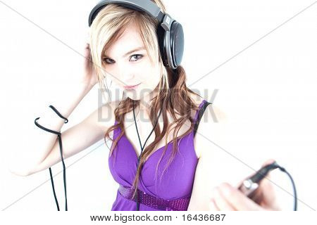 pretty young woman/teenager listening to music on her hi-end headphones, enjoying the groove (color toned image)