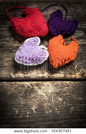Valentine's Day. Colorful knitted hearts. Red heart on the dark old boards. Valentines day. Heart pendant. Red heart. Valentine cards. Space for text. Eighth of March. International Women's Day.