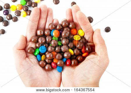 Multi color candy in woman hand isolated on white background
