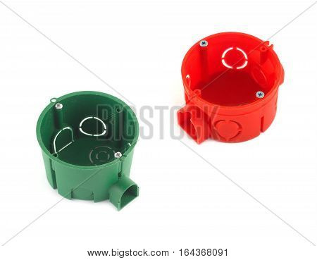 Red and green plastic containers for electric wire mounting isolated on white closeup