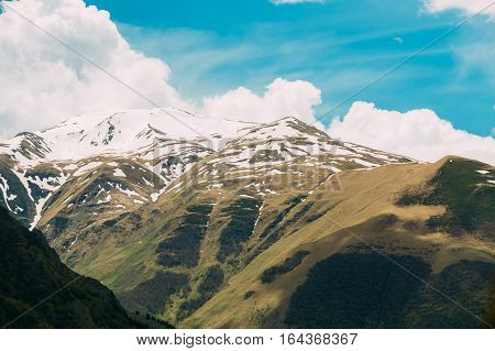 Clouds Fly Low Over Rocks. Mountain Peaks Covered With Snow. Varied Mountain Landscape In Mtskheta-Mtianeti Region, Georgia.