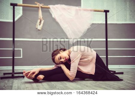 young beautiful graceful ballerina resting in ballet class sitting on the floor ballet shoes a pink skirt and ballet barre in the background