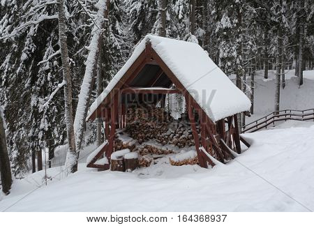 Woodshed with firewood covered with snow in the winter forest. Russian wooden architecture. Valdai. Novgorod region. Russia.