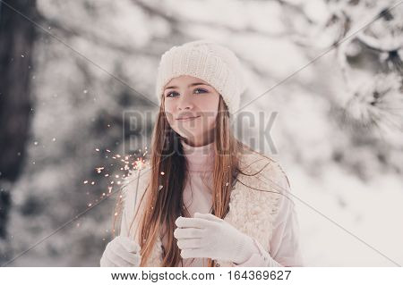 Smiling teen girl 14-16 year old holding sparkler outdoors. Looking at camera. Winter season. Wearing knitted hat and sweater.