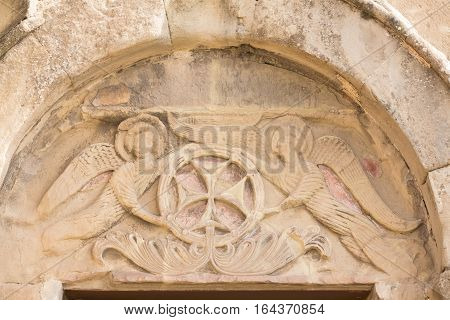 Mtskheta, Georgia. Close View Of Bas-Relief Glorification Of The Cross Crowning The Entrance To The Ancient Jvari Monastery, Georgian Orthodox Church Of Holly Cross, World Heritage By Unesco.